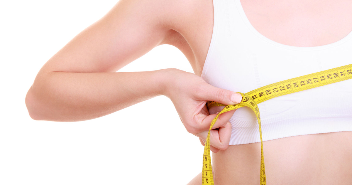 34647659 - time for diet slimming weight loss. health care and healthy nutrition. young fitness woman fit girl with measure tape measuring her bust size chest isolated on white